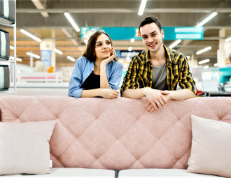 young-love-couple-poses-at-the-pink-couch-in-furniture-store.jpg