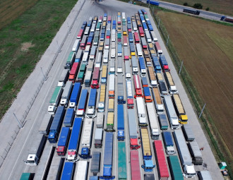 a-pattern-of-many-trucks-taken-down-from-a-height-trucks-lined-up-to-unload-grain-at-the-port.jpg