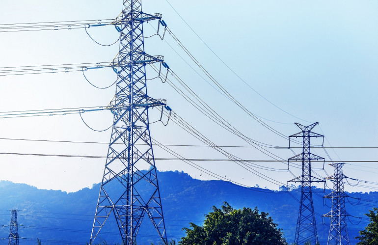 electricity-transmission-pylon-silhouetted-against-blue-sky-at-d.jpg