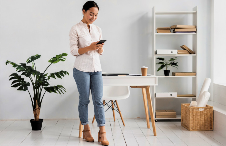 front-view-young-woman-at-office-using-mobile.jpg