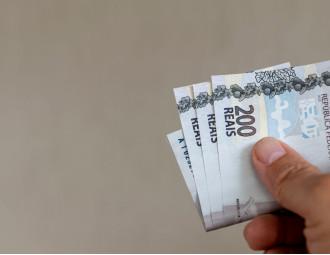 hand-holding-brazilian-money-bills.jpg