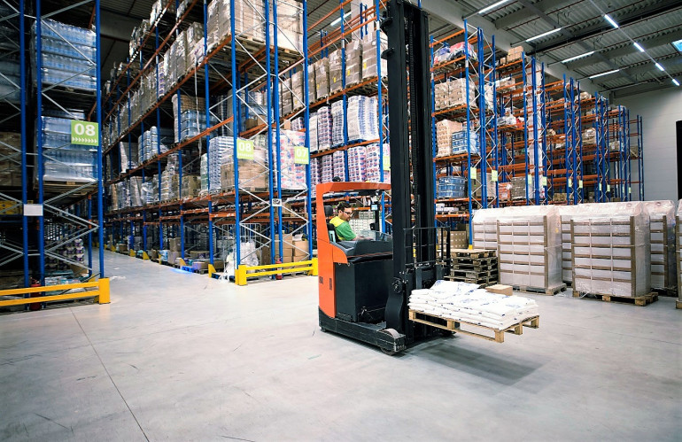 worker-operating-forklift-machine-and-relocating-goods-in-large-warehouse-center.jpg