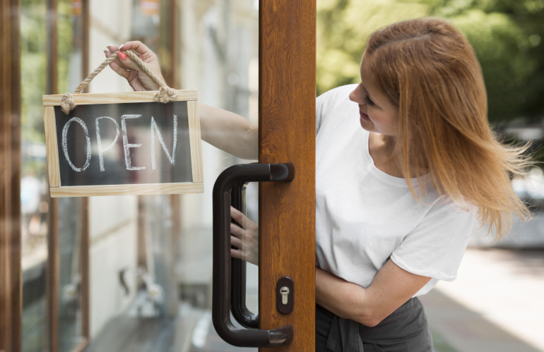 16325-woman-holding-we-are-open-sign_(1)-770x499.jpg
