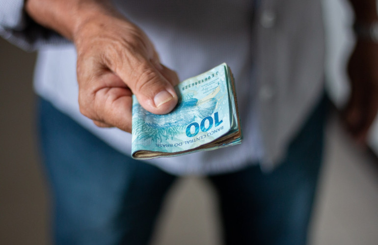 man-holding-brazilian-money-banknotes-by-hand.jpg