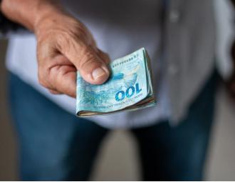 man-holding-brazilian-money.jpg